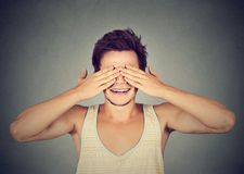 Surprised man covering eyes with hands smiling Royalty Free Stock Photos