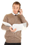 Surprised man with documents and phone. Surprised young well-dressed man in formalwear is talking by phone and looking in a open white file with documents stock image