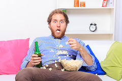 Surprised man eating popcorn on the sofa Stock Photos