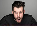 The surprised man and empty blank over gray background Stock Photography