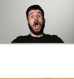 The surprised man and empty blank over gray Royalty Free Stock Images