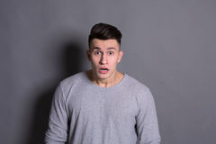 Surprised man expressing amaze on face. Surprised. Wonder man expressing amaze on face, standing on gray background, studio shot stock photography