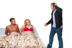 Surprised man finds his wife in bed with another man Stock Images