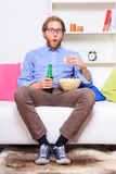 Surprised man in front of TV wirh popcorn and beer Stock Photo