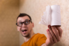 Surprised man in glasses sitting on toilet bowl. Surprised man in glasses sitting on the toilet bowl, out of paper Stock Images