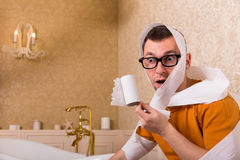 Surprised man in glasses sitting on toilet bowl Royalty Free Stock Images