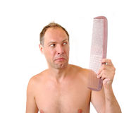 Surprised man hand holding comb near the head Stock Photo