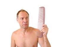 Surprised man hand holding comb near the head. Surprised man hand holding comb near the disheveled head Stock Photo