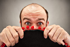 Surprised man hiding behind sombrero hat Royalty Free Stock Images
