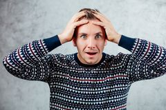 Surprised man holded hands on head on concrete wall stock photography