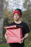 Surprised man holding a Christmas present. Royalty Free Stock Photography
