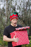 Surprised man holding Christmas presents. Royalty Free Stock Photography