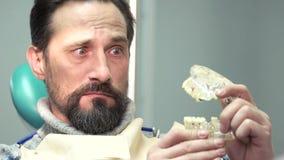 Surprised man holding jaw model.