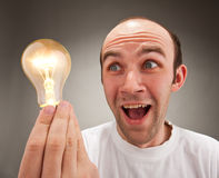 Surprised man holding lighting bulb Royalty Free Stock Photos