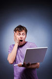 Surprised  man with laptop. Surprised screaming man with laptop in studio Stock Photo