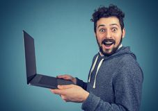 Surprised man with laptop computer. Surprised young excited man with laptop computer looking at camera Royalty Free Stock Image