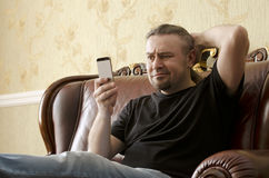 Surprised man looking at cell phone. While sitting on a sofa Stock Images