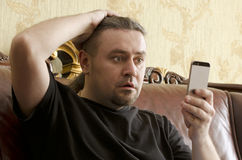 Surprised man looking at cell phone. While sitting on a sofa Royalty Free Stock Image
