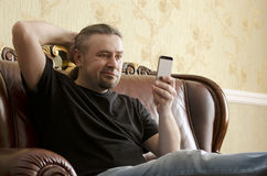 Surprised man looking at cell phone. While sitting on a sofa Stock Photos