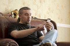 Surprised man looking at cell phone. While sitting on a sofa Royalty Free Stock Photography