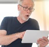 Surprised man looking at his digital tablet, light effect. Surprised mature man looking at his digital tablet, light effect Stock Images