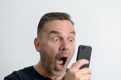 Surprised man looking at his mobile phone Stock Image