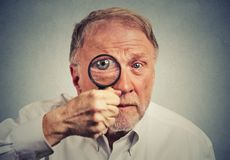 Surprised man looking through a magnifying glass Stock Photos