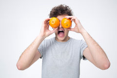 Surprised man looking through oranges Stock Images
