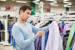 Surprised man looking at price tag of goods Royalty Free Stock Photo