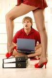 Surprised man looking at sexy woman. Surprised man sitting with computer looking at pretty woman wearing red high heels slippers and baby-doll standing on folder Stock Image