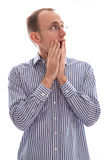 Surprised man looking up over his shoulder with his hands coveri Stock Photo