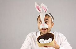 Surprised man in the mask Easter rabbit looking to the side. Easter eggs in hat Royalty Free Stock Photos
