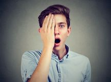 Surprised man, with one eye, covered by hand looking at camera stock photos