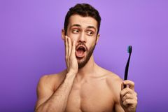 Surprised man with palm on his cheek holding a toothbrush stock image