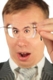 Surprised man peers into spectacles. On white Stock Images