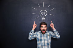 Surprised man pointing up with both hands over chalkboard background. Surprised happy young man with beard pointing up with both hands over chalkboard background Stock Photo
