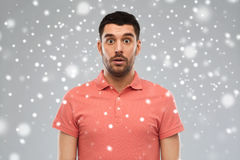 Surprised man in polo t-shirt over snow background Stock Images