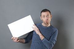 Surprised man presenting empty card for your advert Stock Photo