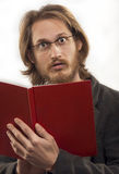 Surprised Man With Red Book. Young blond handsome man wearing glasses is very surprised after reading a book. Shot in studio. Isolated over white Royalty Free Stock Photo