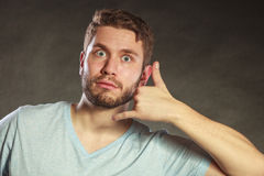 Surprised man showing call me gesture. Stock Images