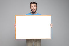 The surprised man showing empty white billboard or Stock Image