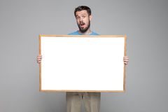 The surprised man showing empty white billboard or Stock Photo