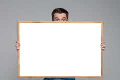 The surprised man showing empty white billboard or Royalty Free Stock Photos