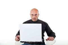 Surprised man sits at the desk and with a laptop Royalty Free Stock Photo
