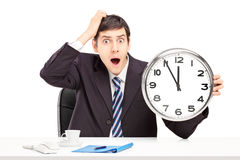 Surprised man sitting in an office and holding a clock Royalty Free Stock Image