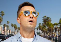 Surprised man in sunglasses over venice beach stock image