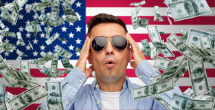 Surprised man under money rain over american flag Stock Photography