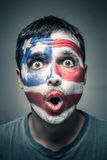 Surprised man with US flag on face. Portrait of surprised man with US flag painted on face Royalty Free Stock Images