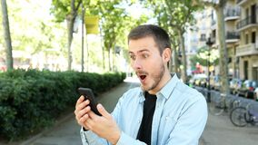 Surprised man uses a phone and looks at camera stock footage