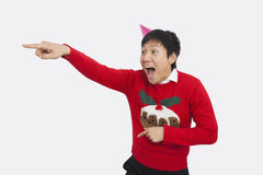 Surprised man wearing Christmas sweater while pointing over white background royalty free stock photo